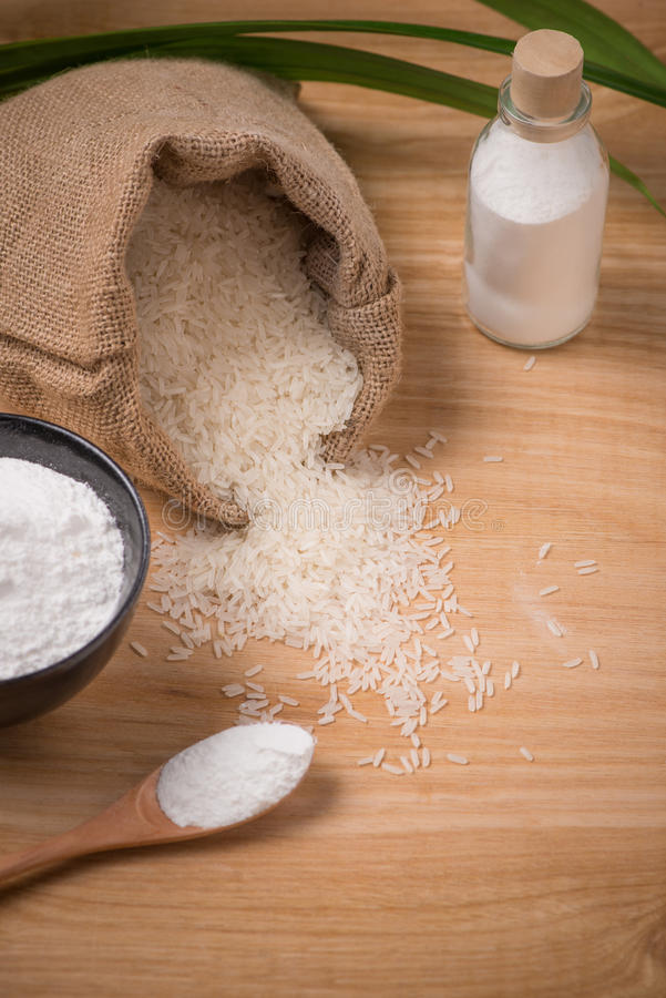 Jasmine white rice in sack and rice flour on wooden table. Jasmine white rice in sack and rice flour on wooden table stock image