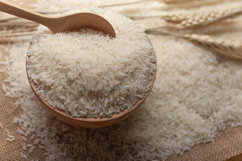 Jasminris i en träbunke, sked och öra av ris på säckvävsäckbakgrund arkivfoton
