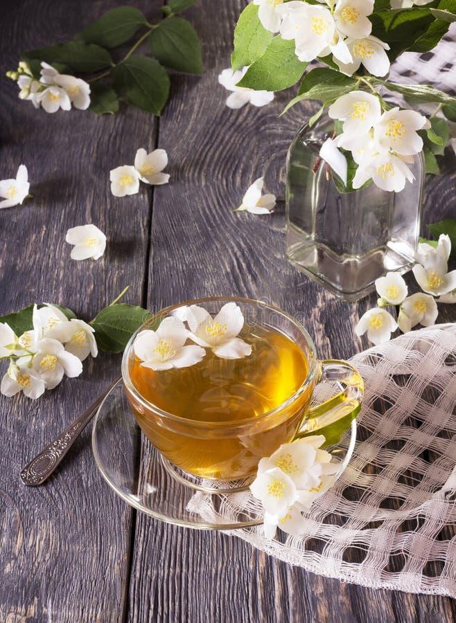 Jasmintee in der Schale und im Blumenstrauß von Blumen im Glasvase auf Tabelle lizenzfreie stockfotografie