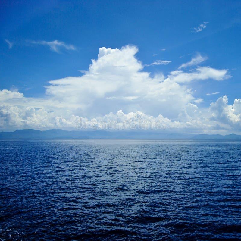 Jasna błękitna morze powierzchnia z czochrami i niebem z chmurami nad nim zdjęcia royalty free