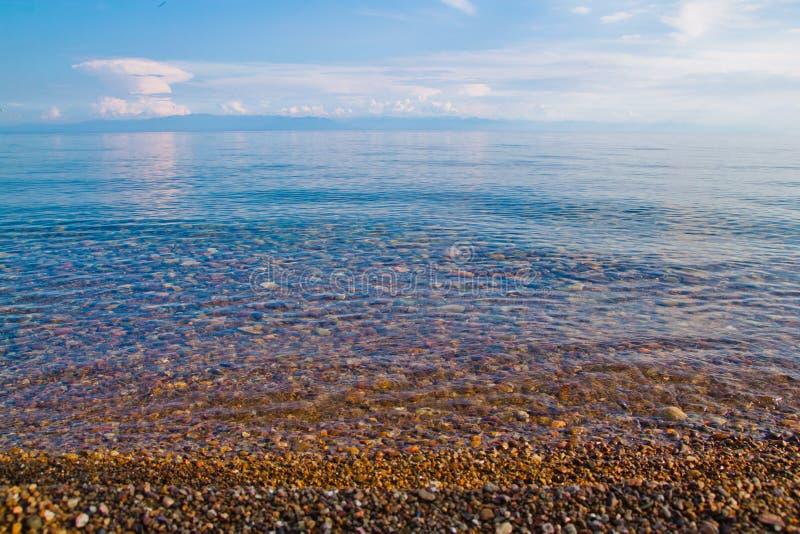Jasna turkus woda, kamienista plaża i niebieskie niebo jako tło, zdjęcie royalty free