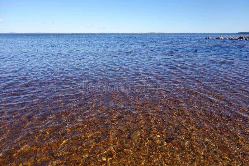 Jasnego czystego jeziora wodni pokazuje pomarańczowi kamienie na podłoga krajobrazu inky błękicie pluskoczą zdjęcia stock