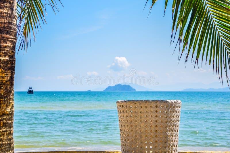 Jasnobr?zowy krzes?o pod kokosowym drzewem dla ogl?da? dennego widok w popo?udniu na pla?y przy Koh Payam, Tajlandia obrazy royalty free