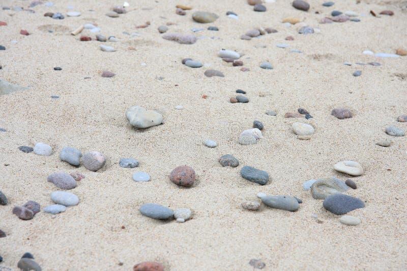 Jasnobrązowy piasek i różni kamienni otoczaki obrazy royalty free