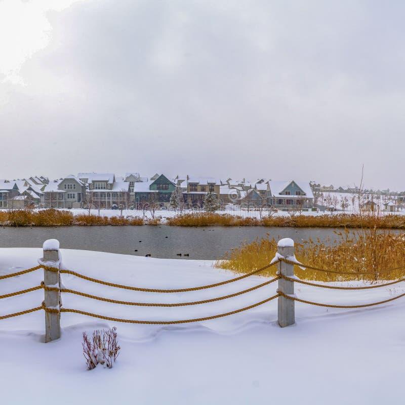 Jasny Kwadratowy klub przegapia jezioro i domy przeciw chmurnemu niebu na mroźnym zima dniu zdjęcie royalty free