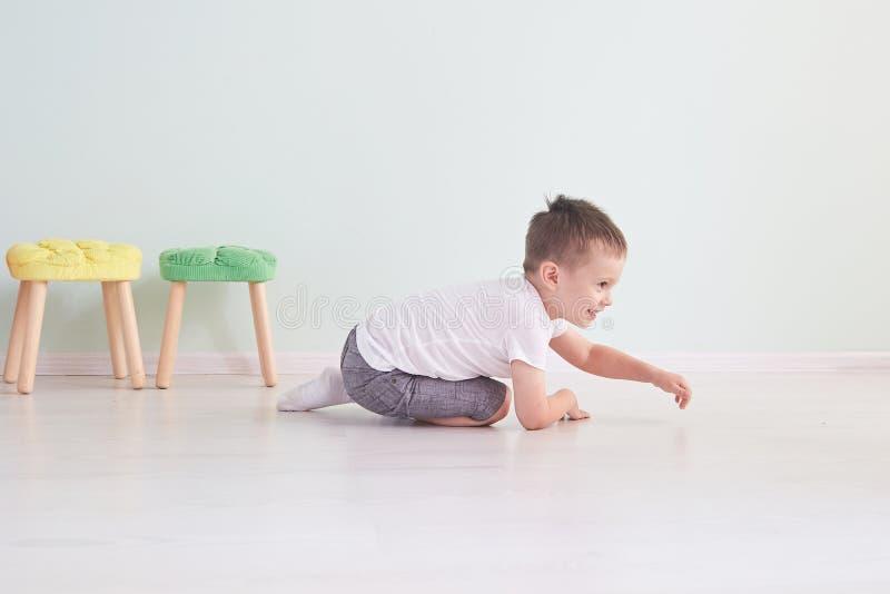 jasny pokój szczęśliwa chłopiec bawić się na podłoga Chłopiec w białej koszulce zdjęcia stock