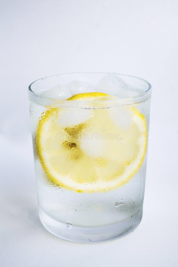 Jasny szkło z zimną wodą, cytryną i lodem, fotografia royalty free