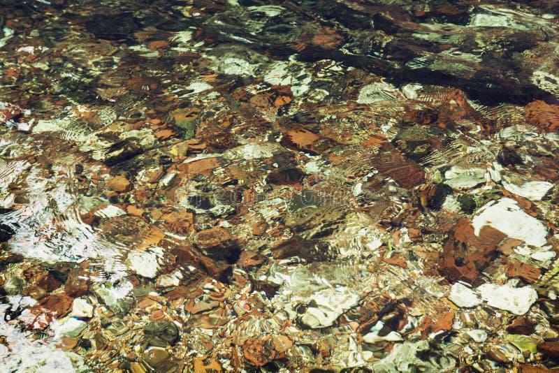 Jasny wodny spływanie nad kamieniami w zatoczce zdjęcie stock