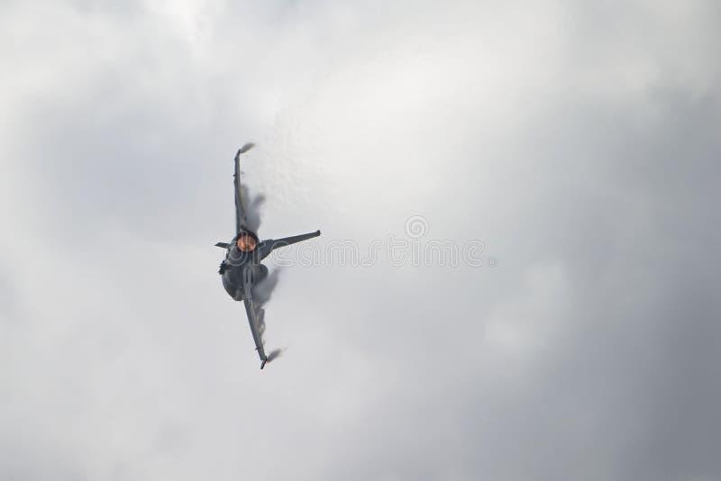 Jato F-16 com dispositivo de pós-combustão sobre e nuvens do vapor que dão forma nas asas fotografia de stock royalty free