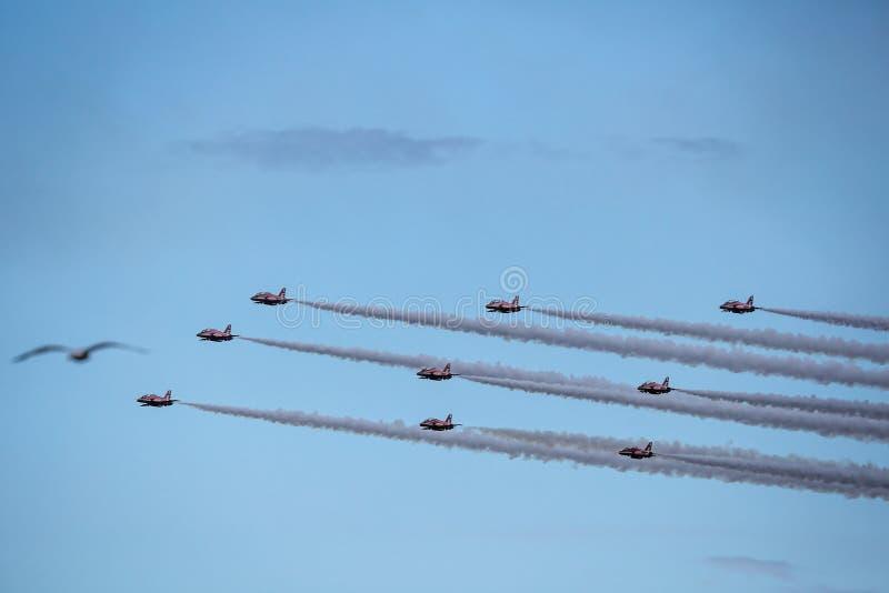 Jatos e helicópteros dos planos que voam durante o airshow imagem de stock