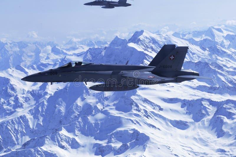 Jatos FA-18 militares da força aérea suíça que acompanha o airplain civil foto de stock royalty free