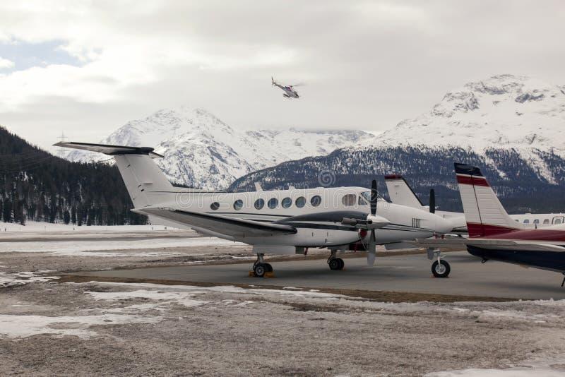 Jatos privados e um helicóptero no aeroporto de St Moritz Switzerland imagem de stock
