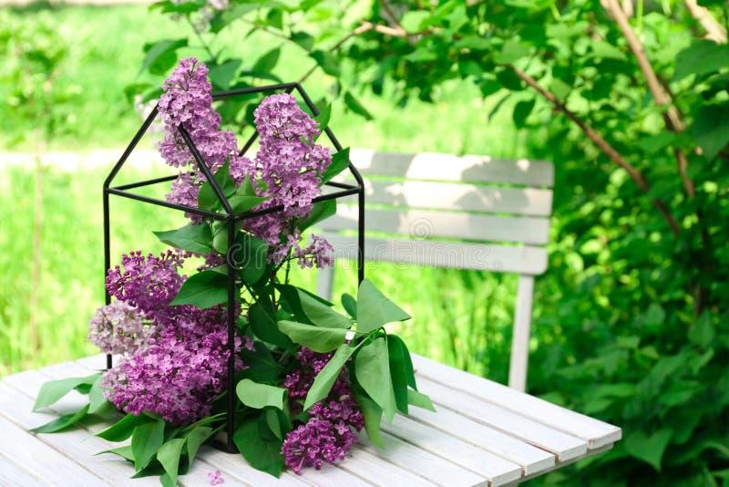 Jaula con las flores hermosas de la lila en la tabla imagen de archivo libre de regalías