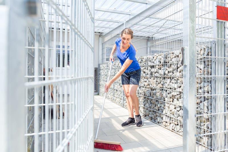 Jaula del perro de la limpieza del Zookeeper en refugio para animales fotos de archivo libres de regalías