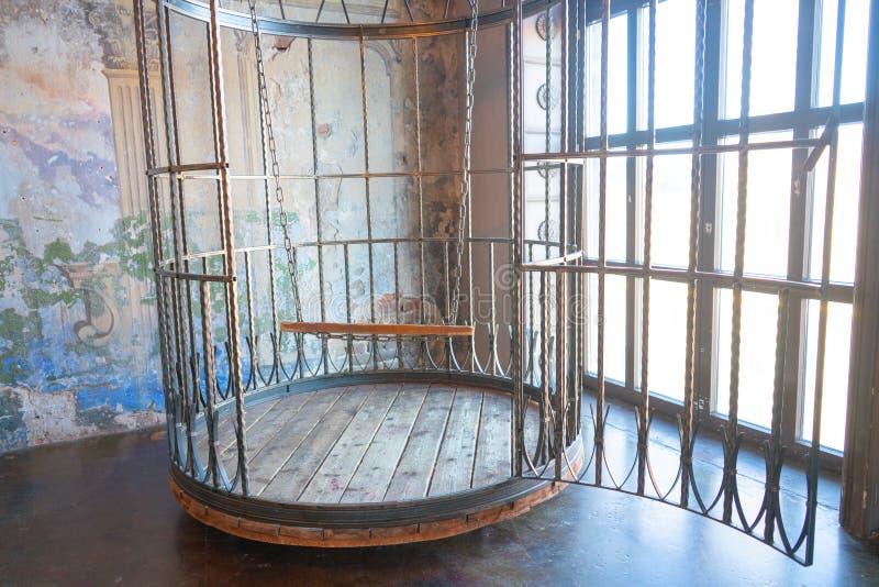 Jaula humana de la ronda enorme del hierro con un interior del oscilación muebles del bdsm hechos del acero imagen de archivo libre de regalías