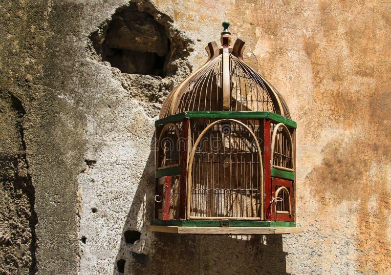 Jaula vacía para los pájaros en una pared vieja, rota fotos de archivo