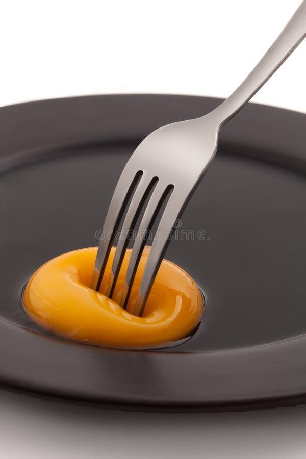 Jaune d'oeuf avec la piquage de fourchette image stock