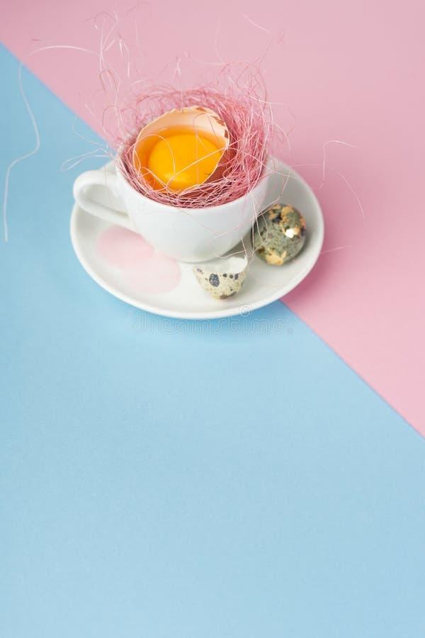 Jaune d'oeuf des oeufs cassés dans la coquille dans une tasse de café blanc sur a photos libres de droits