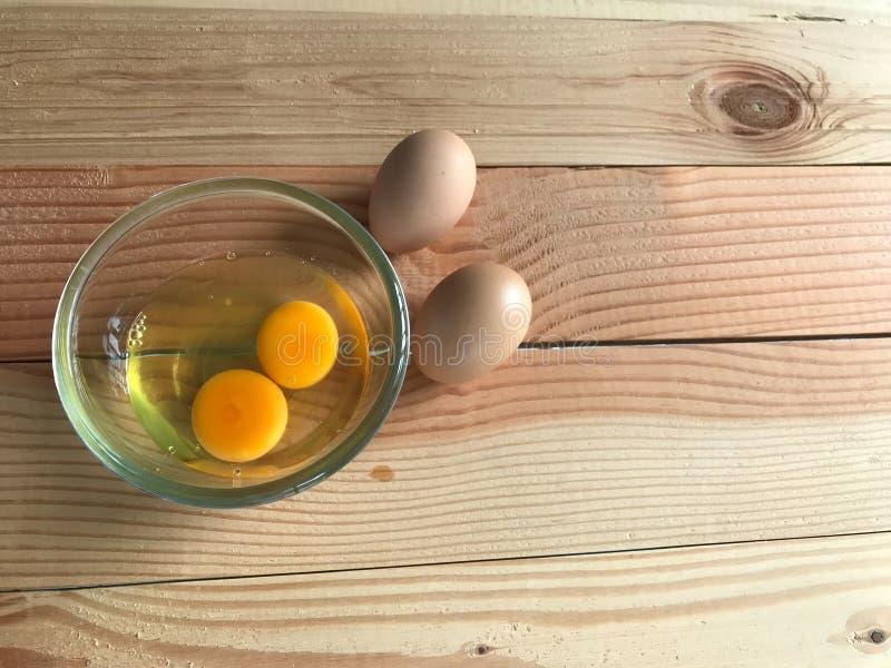 Jaune et blanc d'oeuf frais du poulet deux en une tasse en verre et des deux oeufs différents images libres de droits