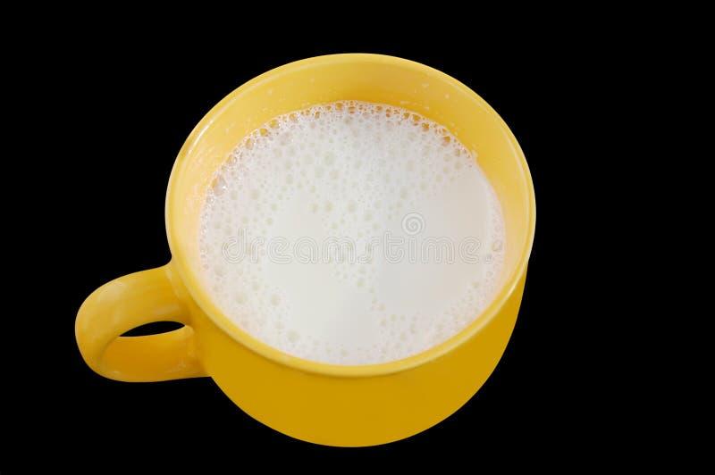 Lait frais dans la grande tasse jaune sur le fond noir.