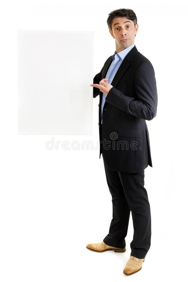 Jaunty salesman pointing to a blank sign. Jaunty salesman or business professional in a stylish suit standing pointing to a blank sign that he is holding in his stock photos