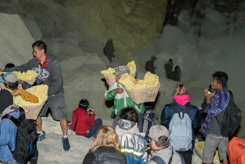 JAVA, INDONÉSIA - AGOSTO, 9, 2016 - os mineiros que levam o enxofre de Ijen Volcano Blue arde na noite fotos de stock