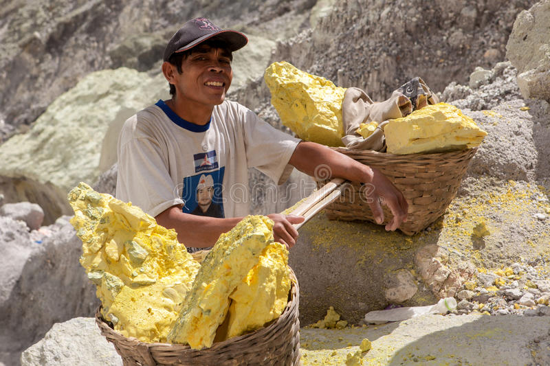 Java/Indonesia - May 8, 2015: Sulfur miner in. Java/Indonesia - May 8, 2015: Sulfur miner in Ijen volcano crater at Java island in Indonesia royalty free stock photo