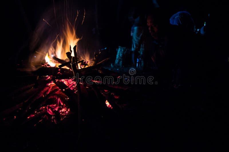 JAVA-ORIENTALE, INDONÉSIE EN JANVIER 2017 : Homme indonésien s'asseyant devant le feu de camp après session de ressac photographie stock