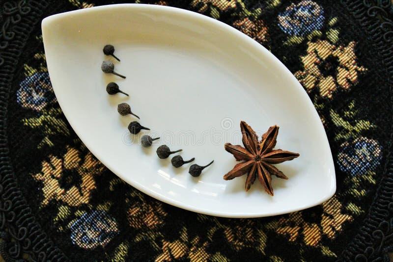 Java peppar och stjärnaanis på en dekorativ platta arkivfoto
