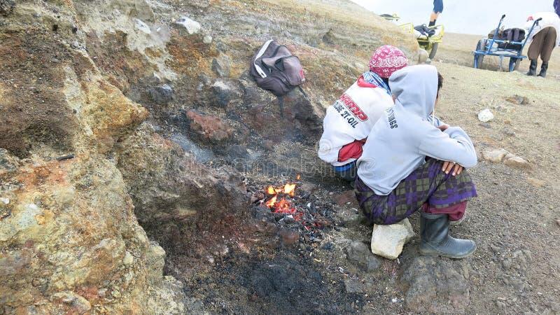 Javanese svavelgruvarbetare som sitter uppe på den aktiva Kawah Ijen vulkan royaltyfri bild