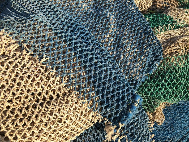 Background. Fishing nets drying in the sun. Javea, Alicante / Spain abstract pattern of green, blue and beige fishnets drying in a heap on the quayside royalty free stock images