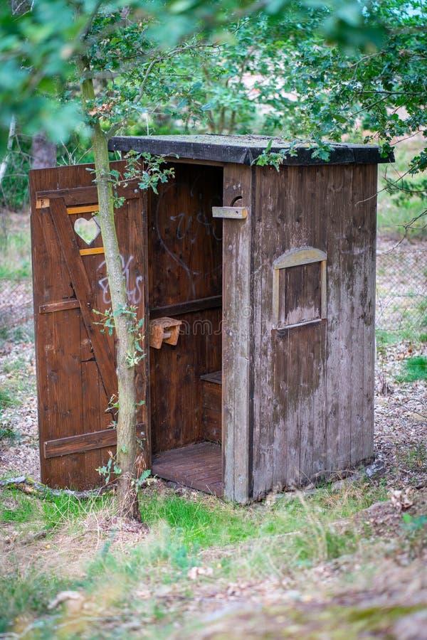 Jawna drewniana outhouse toaleta z kierową wycinanką w drzwi zdjęcia stock