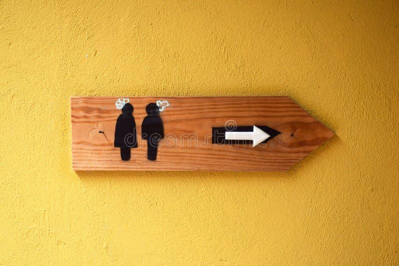 Jawna toaleta podpisuje z strzała na kolor żółty ścianie obraz stock