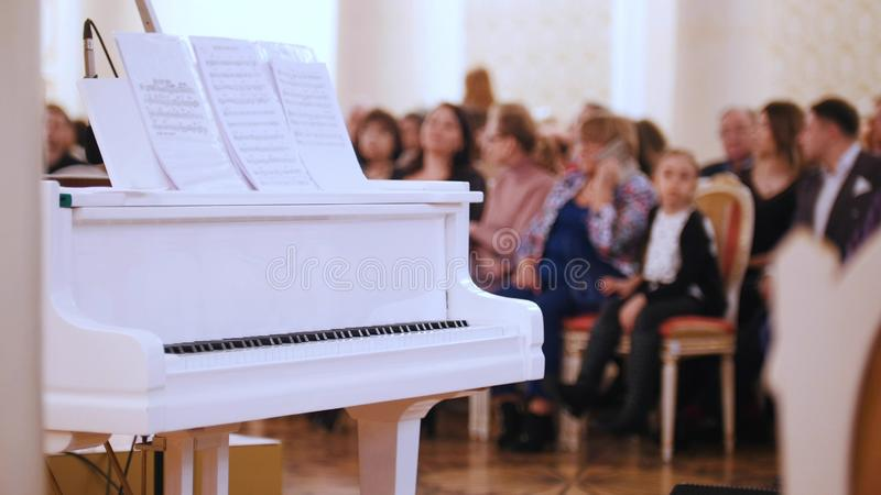 A jazz concert in the concert hall. Piano on the foreground and audience on a background royalty free stock image