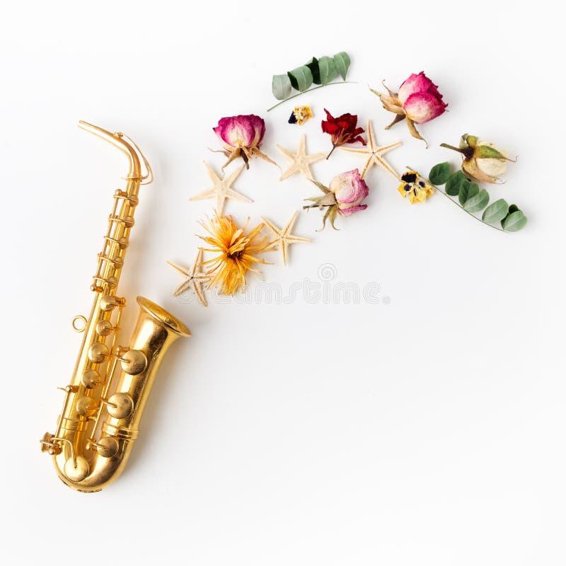 Jazz Day Saxofoon met bloemen Vlak leg, hoogste mening royalty-vrije stock fotografie