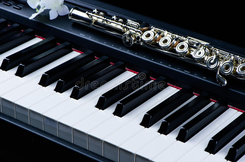 Jazz music instrument flute and piano keyboard close up with flower stock photography