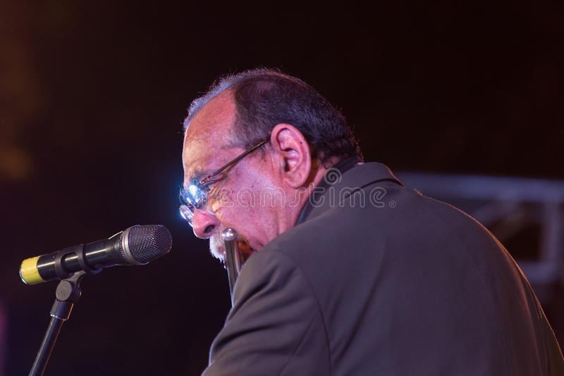 Jazz musician Ernie Watts performing in India. Bangalore, India - February 10, 2018: American Jazz musician Ernie Watts plays the flute as he performs onstage in royalty free stock photography