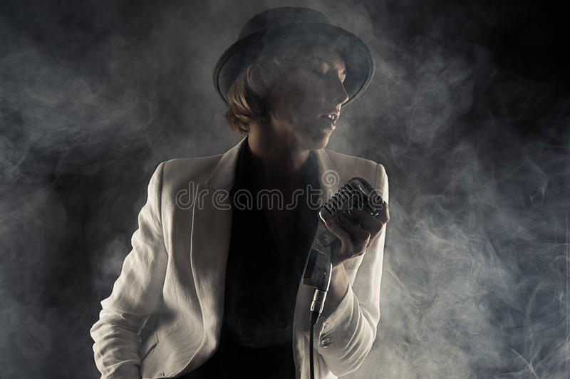 Jazz singer woman with retro microphone in smoke. On black background stock photos