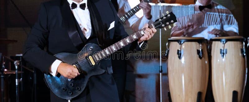 Jazzbandleistung Nahaufnahme Ein abstrakter Mann in einer strengen Klage spielt die Gitarre vor Ort im Vordergrund Trommeln in stockfoto