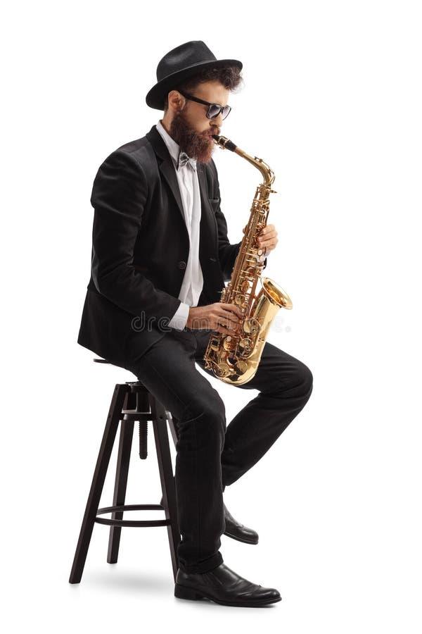 Jazzmusicus het spelen saxofoon en het zitten op stoel stock afbeelding