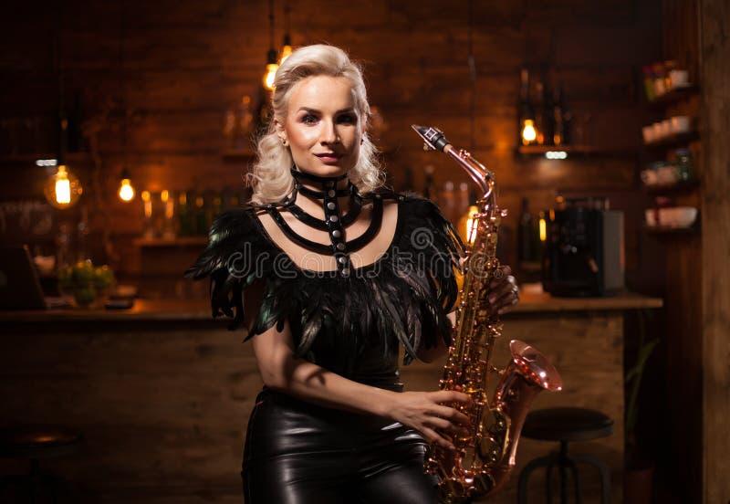 Jazzmusik utförde vid en härlig ung kvinna i en tappningbar på hennes saxofon royaltyfri bild
