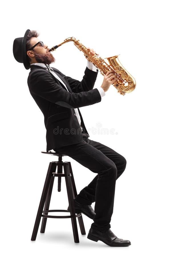 Jazzmusiker som placeras på en stol som spelar en saxofon royaltyfri foto