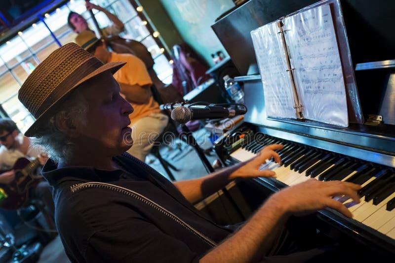 Jazzmusiker som spelar pianot på den prickiga Cat Music Club i staden av New Orleans, Louisiana arkivbild