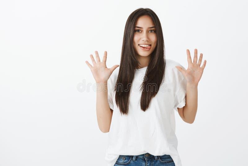 Jazzowe ręki robią dniu jaskrawy Dziecięca figlarnie śmieszna dziewczyna z długim ciemnym włosy w przypadkowym stroju, podnosi pa fotografia stock