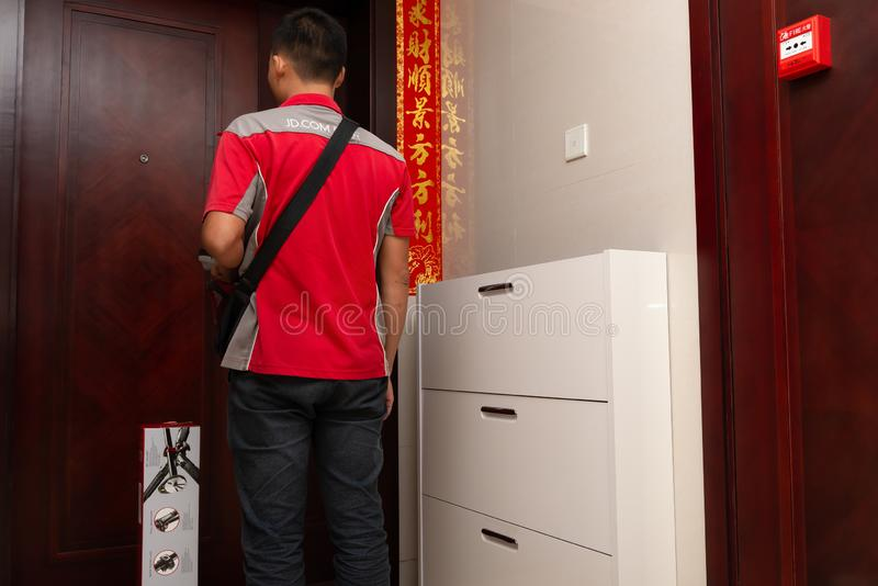 JD.com courier delivering a parcel to the customers home.Nov 11 is the shopping day in China and many online shops sale things in. Zhongshan,China-November 2 stock photos