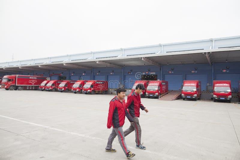 JD.com shipping trucks. Gu'an, China - June 14, 2016: JD.com staff walking at shipping dock at the Northeast China based Gu'an warehouse and distribution royalty free stock image