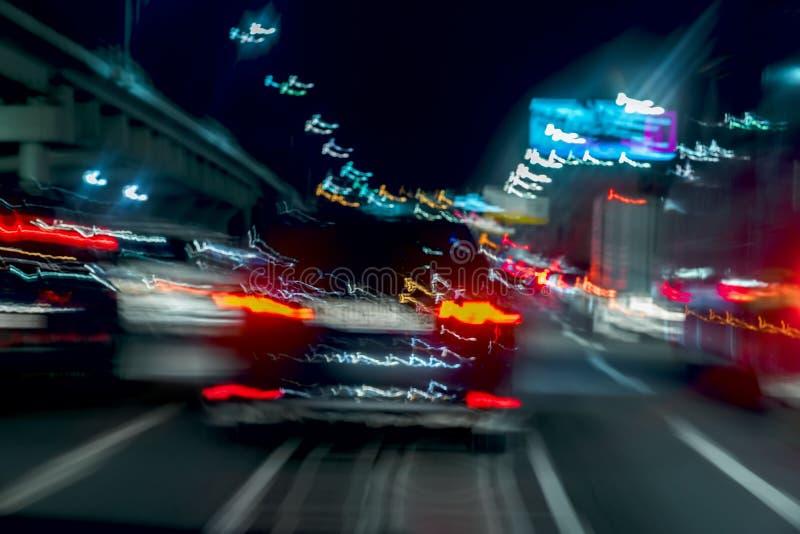 Jeûnez en conduisant le trafic la nuit, couleurs bleues Soustrayez le fond brouillé de la voiture mobile urbaine avec les feux de photos stock