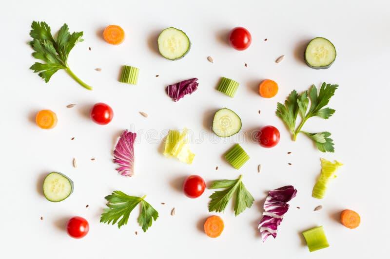 Jeść deseniowy z surowymi składnikami sałatka, sałata liście, ogórki, czerwoni pomidory, marchewki, seler i ziarna, obraz royalty free