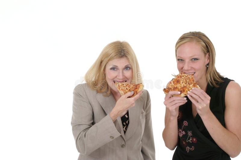 jeść pizzy przedsiębiorstw dwie kobiety. obraz stock