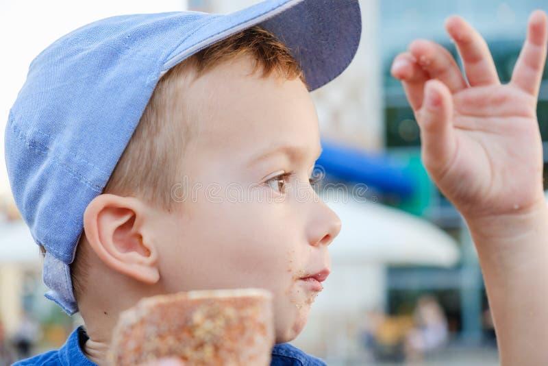Jeść rolkę jest istnym przyjemnością dla chłopiec Weekend, dziecko w parku obrazy royalty free